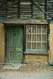 Weathered green door with an aged house. Weathered green door with an aged stone house, home related Royalty Free Stock Image