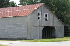 Weathered grey Amish barn with red metal roof Stock Photography