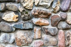 Weathered grunge rough stone wall as background texture. Close up stock photography