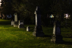 Weathered headstones at night time Stock Photo