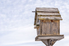 Weathered homemade birdhouse on a stand Royalty Free Stock Images