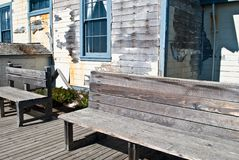 Weathered House and Benches. Weathered House with Hardwood Paneling and Wooden Benches Royalty Free Stock Photography