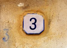Weathered house number 3 three on old stone wall stock photos