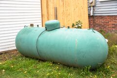 Old green propane tank in backyard of a house