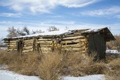 Old log barn in snow Royalty Free Stock Photo