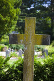 Weathered marble cross on grave. Stock Photo