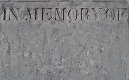 Weathered gravestone with the words - in memory of - engraved in the stonework royalty free stock photo