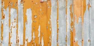 Weathered metal wall with peeling orange paint stock image