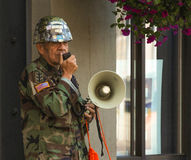 Weathered Military Veteran Speaking to the Masses. An elderly military veteran proclaims his views with a hand held megaphone on the Seattle street corner. He is royalty free stock photo