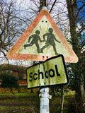 Weathered moss covered school signs. Weathered grunge and moss covered school kids crossing signs on a pole with winter bare trees in the background against a Royalty Free Stock Photos