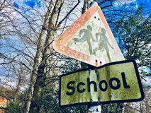 Weathered moss covered school signs. Weathered grunge and moss covered school kids crossing signs on a pole with winter bare trees in the background against a Stock Images