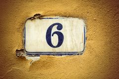 Number six enamel door number on plaster wall Stock Image
