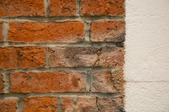 Weathered old bricks opposed new white wall stock image