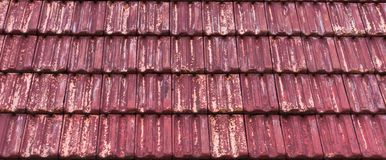 Weathered and old red colored classic stone roof tiling with faded out colors, architecture texture pattern background. A weathered and old red colored classic royalty free stock photography
