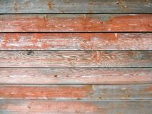 Weathered old wood texture with red flaked paint. Wooden surface with a row of rusty metallic rivets. For use as a background royalty free stock photography