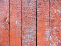 Weathered old wood texture with red flaked paint. Royalty Free Stock Images