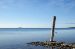 Weathered old wooden pole by a flat rock coast Royalty Free Stock Photos