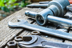 On weathered old wooden surface lie the , oily wrenches. On weathered old wooden surface lie the old, oily wrenches. Near scattered old rusty nuts Stock Image