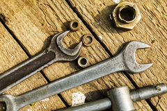 On weathered old wooden surface lie the , oily wrenches. On weathered old wooden surface lie the old, oily wrenches. Near scattered old rusty nuts Stock Photos