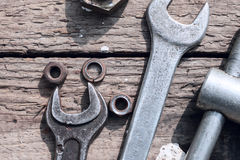 On weathered old wooden surface lie the , oily wrenches. On weathered old wooden surface lie the old, oily wrenches. Near scattered old rusty nuts Stock Photo