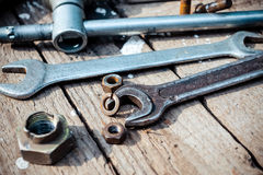 On weathered old wooden surface lie the , oily wrenches. On weathered old wooden surface lie the old, oily wrenches. Near scattered old rusty nuts Royalty Free Stock Images