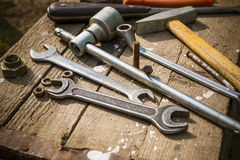 On weathered old wooden surface lie the , oily wrenches. On weathered old wooden surface lie the old, oily wrenches. Near scattered old rusty nuts. Imitation of Stock Image