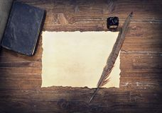 Weathered paper, ink and feather on wooden table Royalty Free Stock Photo