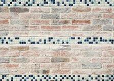 Weathered pastel paved brick and ceramic tile feature wall. Vintage bricks with white and blue checkered ceramic highlights, shot outdoors with natural light Royalty Free Stock Photo