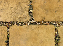 Weathered paving stones. Weathered paving slabs, surrounded by golden gravel, with weeds between the slabs stock images