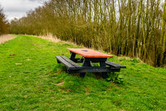 Weathered picnic table with an orange table top on a Dutch dike Stock Photography