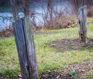 Weathered Posts At canonsburg Lake. Old wood needing replacement with lake water in background winter season Royalty Free Stock Image