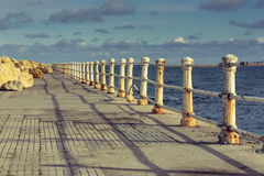 Weathered railings and seafront promenade Stock Photo