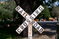 Weathered Railroad Crossing Sign. Railroad crossing sign with black lettering on a white background. Sign posted at park with a miniature tourist railroad Royalty Free Stock Photography