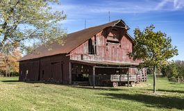 A weathered red barn in rural area. A weathered red barn in rural America with a blue sky and white clouds Stock Photos