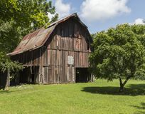 Weathered red barn in a rural setting. Weathered red barn in a field with blue sky and white puffy clouds Royalty Free Stock Photos