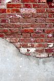 Weathered red brick wall half covered with cement Royalty Free Stock Photos