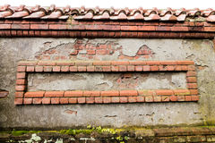Weathered red bricks are decoratively situated in wall. For background texture royalty free stock photo