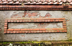 Weathered red bricks are decoratively situated in wall. For background texture stock image