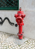 Weathered red fire hydrant near a cement wall Royalty Free Stock Image