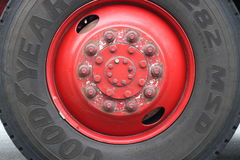 Weathered red metal hub cap on Good Year tire. Stock Images