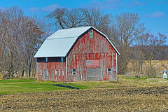 Weathered Red Wood Barn with a Flag Stock Photos