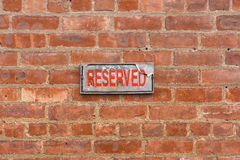 Weathered reserved sign on brick wall Stock Image