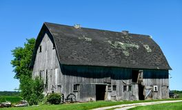 Weathered Rock County Barn. This is a Summer picture of an oldl weathered multiple-purpose framed barn against a blue sky located in Rock County, Wisconsin. This royalty free stock photo