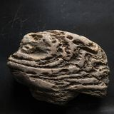 Weathered Rock On Dark Scratched Background. Legendary Artifact of Power, Courage and Healing Symbol Concept stock photo