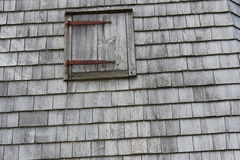 Weathered. Rusty hinged weathered boarded window and shingles Stock Images