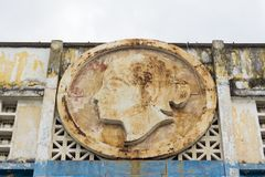 Weathered rusty house facade with woman head relief. Weathered rusty house facade with soviet woman head relief stock image