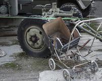 Weathered rusty vintage baby pram and military vehicle on courtyard.  royalty free stock images