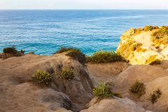 Weathered sandstone path to cliff edge with western wallflower. Overlooking pacific ocean stock photos