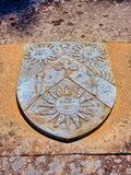 Weathered Sun God Shield on Old Grave Stone. A weathered shield with sun god emblems on an old grave top stone slab in disused cemetery, South Head Cemetery stock photography