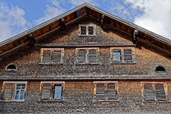 Weathered shingle house facade. The weathered facade of an old shingle house. Wooden shutters at the windows. Traditional Austrian architecture stock photos